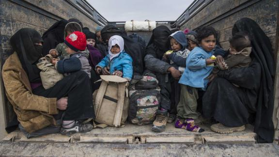 Women and children who fled the Islamic State group's embattled holdout of Baghouz wait in the back of a truck in the eastern Syrian province of Deir Ezzor, on February 14, 2019.