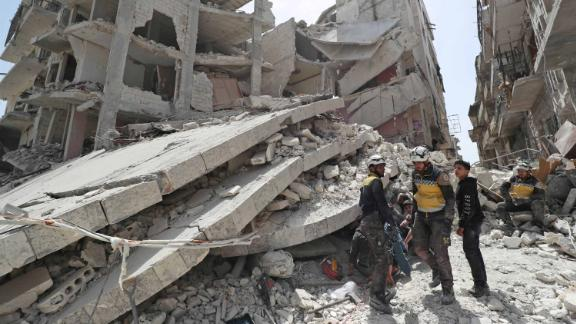 "Members of the Syrian Civil Defence, also known as the ""White Helmets,"" search the rubble of a collapsed building following an explosion in the town of Jisr al-Shughur on April 24, 2019."