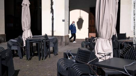 A man walks near a closed bar on March 17, 2021 at the Piazza Vittorio in Turin.