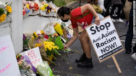 Activists place flowers during a protest in Atlanta against violence targeting women and Asians on Thursday, March 18.