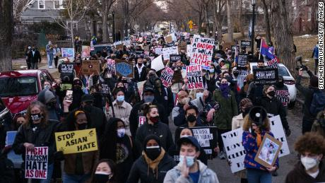 People march through a neighborhood in Minneapolis, Minnesota, on March 18, 2021, to protest anti-Asian violence.