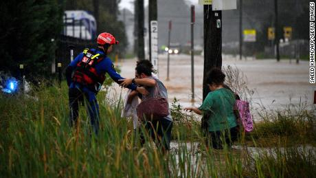 A rescue worker helps residents cross a flooded road in western Sydney on March 20
