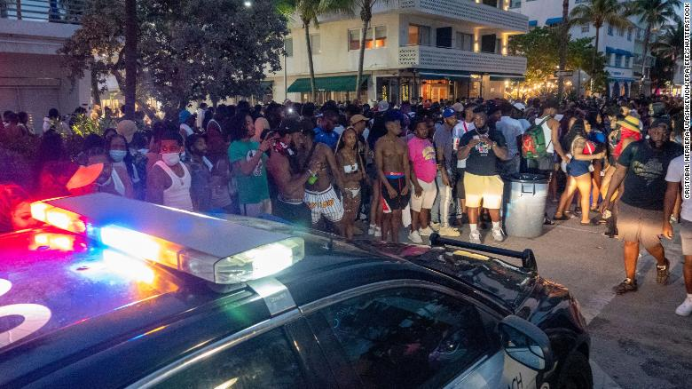 Miami Beach Police Department officers enforce an 8 p.m. curfew on Saturday night.