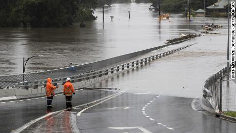 Traffic controllers stand at the Hawkesbury River Bridge submerged by floodwaters in Windsor, New South Wales, on March 22.