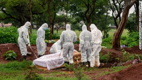 Funeral directors lower the coffin of a person who died of Covid-19 at the Glen Forest cemetery in Harare, Zimbabwe, on January 14, 2021.