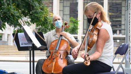 Principal Cello Carter Bray, and New York Philharmonic Principal Viola Cynthia Phelps hold a surprise free performance outside Lincoln Center in New York City on July 7, 2020.  (Photo by Noam Galai / Getty Image)