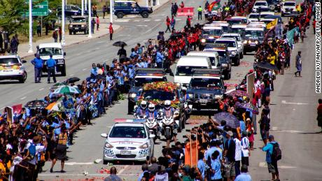 People line up as police escort a hearse carring the coffin of Papua New Guinea's first Prime Minister Michael Somare in Port Moresby on March 11.