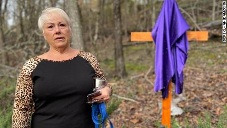 Dena Cook stands by the cross her husband built for their backyard.