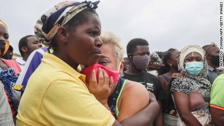 A woman cries as she waits for her son to arrive in Pemba on April 1, 2021, from the boat of evacuees from Palma.