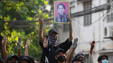 Anti-coup demonstrators raise the three finger of resistance and a portrait of deposed leader Aung San Suu Kyi as prepare to confront police during a protest in Tarmwe township, Yangon on April 1.