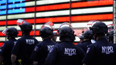NYPD police officers watch demonstrators in Times Square on June 1, 2020. Protests over the police killing of George Floyd in Minneapolis often forced police departments to pull cops out of high-crime neighborhoods.