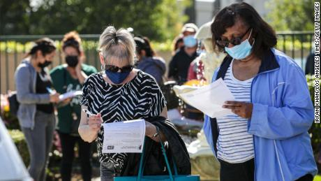 Maureen Brackett, left, and Beulah Knowles fill out medical forms while waiting in line for a Covid-19 vaccine at a Covid-19 vaccine clinic help by L.A. County Department of Public Health for seniors at Whispering Fountains Senior Living Community on March 31, 2021 in Lakewood, California