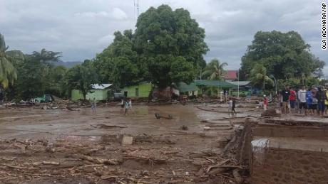 Residents inspect the damage at a village hit by flash floods in East Flores, Indonesia