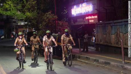 On 3 April, after the new evening curfew is implemented, police personnel patrol in Pune, India.