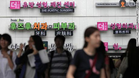 Signs for plastic surgery clinics are displayed on a building in the Apgujeong-dong area of Gangnam district in Seoul, South Korea, on August 3, 2013.