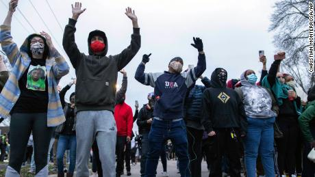 People raise their hands in front of authorities on Sunday, April 11, 2021, in Brooklyn Center, Minnesota.