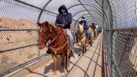 Voters on horseback, riding with Protect the Sacred's Ride to the Polls Election Day initiative, trot over a bridge entering Kayenta, Arizona, on Election Day to cast their votes.