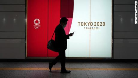 A man wearing a protective mask to stop the spread of the coronavirus walks near ads for the Tokyo 2020 Olympics on Tuesday, April 6, in Tokyo.