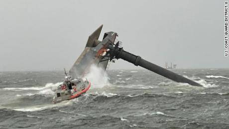 A Coast Guard boat heads toward the capsized commercial liftboat while searching for people in the water on Tuesday, April 13.