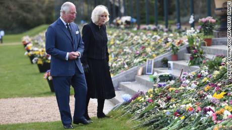 Prince Charles and the Duchess of Cornwall view the flowers and messages of condolence left outside Buckingham Palace.