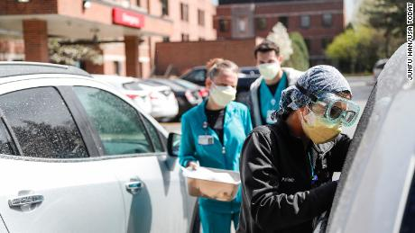 Emergency technicians test patients for Covid-19 outside the emergency entrance to Beaumont Hospital in Grosse Pointe, Michigan, Thursday.