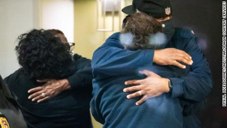People hug after learning that their loved one is safe after a person shot and killed eight people inside a FedEx building in Indianapolis.