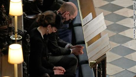 Prince William and his wife Catherine, the Duchess of Cambridge, bow their heads in prayer during the ceremony.
