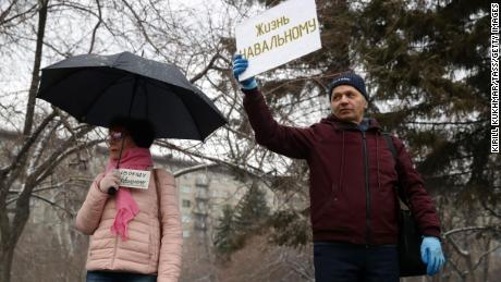 """Supporters of Alexey Navalny hold signs reading """"Freedom to Navalny"""" (left) and """"Let Navalny Live"""" as they take part in an unauthorized rally in Lenina Square, Novosibirsk."""