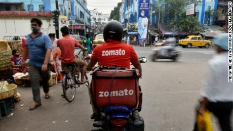 A Zomato delivery rider waits to cross a road in Kolkata, India.