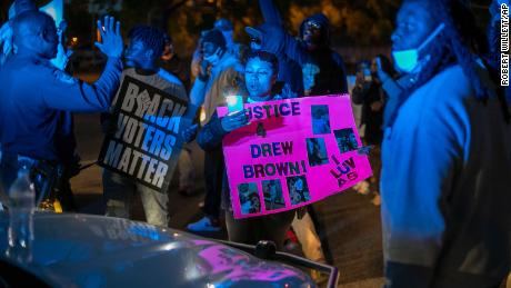 Police work to disperse demonstrators after they surrounded an Elizabeth City police car.