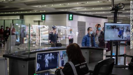 Airport health staff monitor the body temperatures of arriving passengers with thermal scanners in an arrival hall inside Hong Kong International Airport on February 21, 2020.