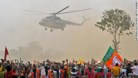 Supporters of Modi's Bharatiya Janata Party (BJP) wave towards a helicopter carrying the prime minister as he arrives at a rally on April 10.
