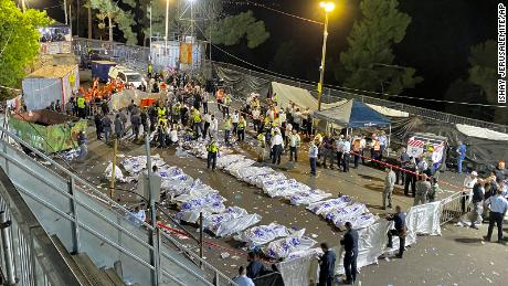 Israeli security officials and rescuers stand around the bodies of victims who died during celebrations at Mount Meron in northern Israel, on April 30, 2021.