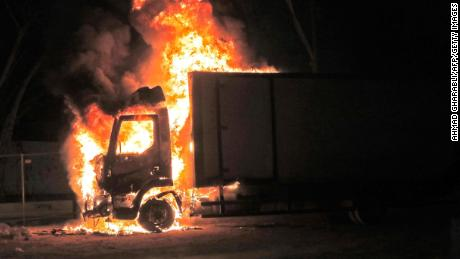 A truck burns near the entrance to the city of Lod.