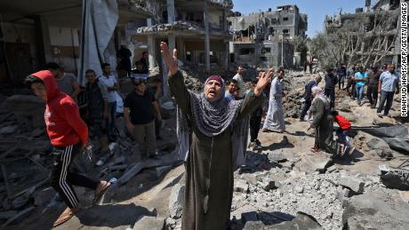 A Palestinian woman reacts as people assess the damage caused by Israeli air strikes in Beit Hanun, Gaza, on Friday, May 14.