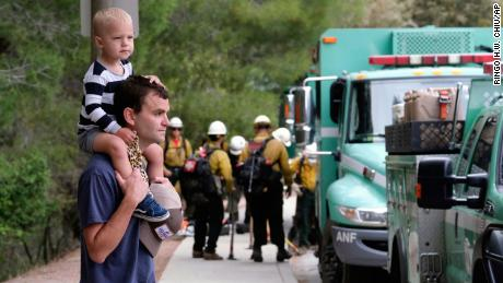 Pacific Palisades resident Mike Sutton, 31, and his son, Tommy, 2, watch the deployment of firefighters Sunday.