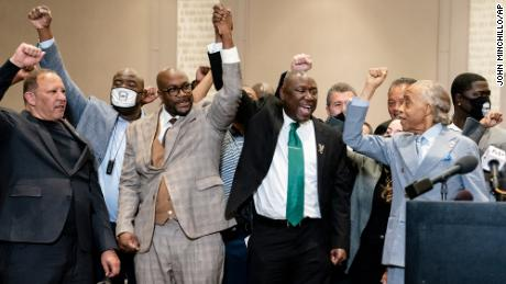 Ben Crump,  flanked by Philonise Floyd, brother of George Floyd, center left, and the Rev. Al Sharpton, right, raise their hands in triumph after the murder conviction against former Minneapolis police Officer Derek Chauvin in the killing of George Floyd.