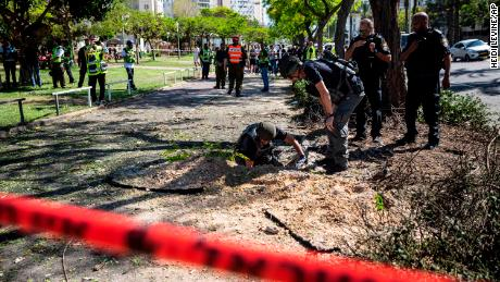An Israeli bomb squad unit inspect the site where a rocket fired from Gaza hit a sidewalk in Ashdod, Israel, on Wednesday, May 19.