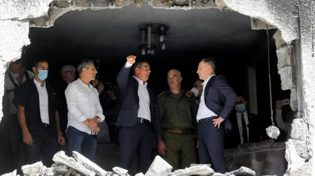 German Foreign Minister Heiko Maas, right, listens to his Israeli counterpart, Gabi Ashkenazi, center, during a visit Thursday to a building in the Israeli city of Petah Tikva that was hit by rocket fire.