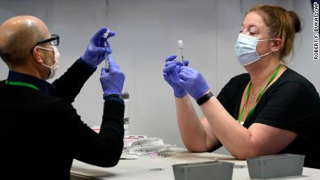 Pharmacy technicians fill syringes with Pfizer's Covid-19 vaccine on March 2 at the Portland Expo in Portland, Maine