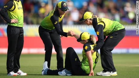 Perry is helped to her feet during the Cricket World Cup match between Australia and New Zealand in Melbourne last year.