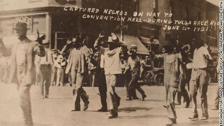 Men walk with their hands raised during the Tulsa massacre on June 1, 1921.