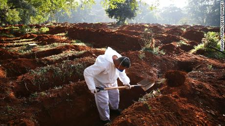 A cemetery worker digs graves for the bodies of people who died of Covid-19 in Sao Paulo this month.