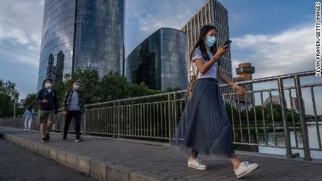 Le persone indossano maschere protettive mentre attraversano un ponte sul fiume Liangma il 24 maggio a Pechino, in Cina.