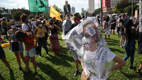 A protester wears a sign accusing Bolsonaro of genocide.