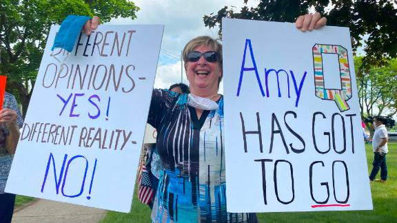 """Protesters made signs calling Fachinello """"Amy Q"""" because of the controversy surrounding her QAnon-related posts."""