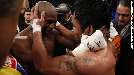 Mayweather embraces Manny Pacquiao after defeating him in their welterweight unification bout.
