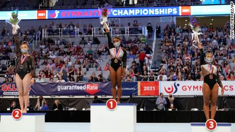 Sunisa Lee, from left, Simone Biles and Jordan Chiles, right, step up to their respective podiums after finishing in the top three after the U.S. Gymnastics Championships on Sunday, June 6, 2021, in Fort Worth, Texas.