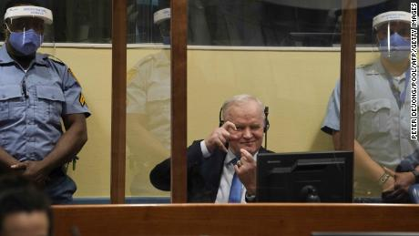 Mladic imitates taking pictures as he sits in the defendant box prior to the hearing of the final verdict on June 8.