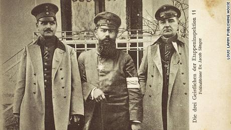 Military Jewish pastor Dr. Jacob Sanger (middle) is shown in this photo postcard, issued from around 1915 to 1916.  A Catholic and Protestant clergy stand on either side.